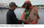 Моряк помогает снять водолазный костюм водолазу (2018 год). Редакционное видео, видеограф А. А. Пирагис / Фотобанк Лори
