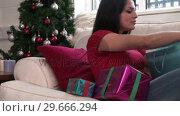 Купить «Woman with Christmas Presents», видеоролик № 29666294, снято 26 февраля 2008 г. (c) Wavebreak Media / Фотобанк Лори