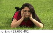 Купить «Woman Lying on Grass», видеоролик № 29666402, снято 26 февраля 2008 г. (c) Wavebreak Media / Фотобанк Лори
