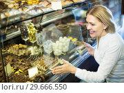 Купить «Woman selecting chocolates and confectionery», фото № 29666550, снято 31 марта 2020 г. (c) Яков Филимонов / Фотобанк Лори