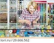 Купить «portrait of female cashier standing at cash desk in embroidery shop», фото № 29666562, снято 19 января 2019 г. (c) Яков Филимонов / Фотобанк Лори