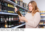 Купить «Portrait of nice woman buying bottle of wine», фото № 29666702, снято 11 апреля 2018 г. (c) Яков Филимонов / Фотобанк Лори