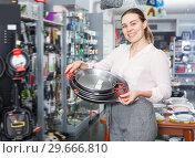 Купить «Glad woman is choosing set of stewpot», фото № 29666810, снято 2 мая 2018 г. (c) Яков Филимонов / Фотобанк Лори