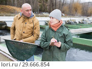 Купить «Owner of sturgeon farm giving instruction to female», фото № 29666854, снято 4 февраля 2018 г. (c) Яков Филимонов / Фотобанк Лори