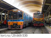 Два пассажирских поезда на  железнодорожном вокзале Hua Lamphong. Бангкок, Таиланд (2019 год). Редакционное фото, фотограф Виктор Карасев / Фотобанк Лори