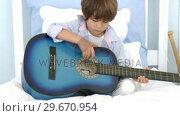 Купить «Little boy playing guitar on bed», видеоролик № 29670954, снято 10 октября 2009 г. (c) Wavebreak Media / Фотобанк Лори