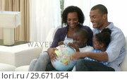 Купить «AfroAmerican family examining a terrestrial globe», видеоролик № 29671054, снято 21 октября 2009 г. (c) Wavebreak Media / Фотобанк Лори