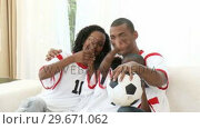 Купить «Family watching a soccer match at home», видеоролик № 29671062, снято 21 октября 2009 г. (c) Wavebreak Media / Фотобанк Лори