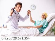 Купить «Young handsome doctor visiting female oncology patient», фото № 29671354, снято 3 октября 2018 г. (c) Elnur / Фотобанк Лори