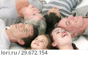 Купить «Happy family lying on floor with heads together», видеоролик № 29672154, снято 20 октября 2009 г. (c) Wavebreak Media / Фотобанк Лори