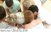 Купить «Teenagers looking at a Globe», видеоролик № 29672310, снято 22 октября 2009 г. (c) Wavebreak Media / Фотобанк Лори