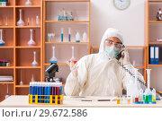 Купить «Young biochemist wearing protective suit working in the lab», фото № 29672586, снято 11 августа 2018 г. (c) Elnur / Фотобанк Лори