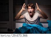 Купить «Young man scared in his bed having nightmares», фото № 29673366, снято 18 сентября 2018 г. (c) Elnur / Фотобанк Лори