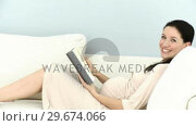 Купить «Cheerful pregnant woman reading a book», видеоролик № 29674066, снято 18 июля 2019 г. (c) Wavebreak Media / Фотобанк Лори