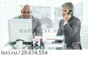 Купить «Two angry businessman on phone working at a computer», видеоролик № 29674554, снято 23 марта 2019 г. (c) Wavebreak Media / Фотобанк Лори