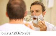 Купить «Man shaving himself in front of a mirror», видеоролик № 29675938, снято 7 ноября 2010 г. (c) Wavebreak Media / Фотобанк Лори