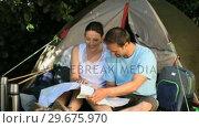 Купить «Couple looking at a map near a tent», видеоролик № 29675970, снято 7 ноября 2010 г. (c) Wavebreak Media / Фотобанк Лори
