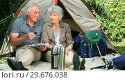Купить «Seniors looking at a map sitting near a tent», видеоролик № 29676038, снято 7 ноября 2010 г. (c) Wavebreak Media / Фотобанк Лори