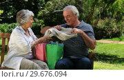 Senior couple looking at purchasing on a bench. Стоковое видео, агентство Wavebreak Media / Фотобанк Лори
