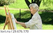 Elderly female painting a canvas. Стоковое видео, агентство Wavebreak Media / Фотобанк Лори