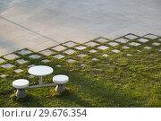 Купить «Вид из-за стекол окна Технограда ВДНХ (ВВЦ) на благоустроенный газон со столом и стульями. 2018», эксклюзивное фото № 29676354, снято 6 ноября 2018 г. (c) Кузин Алексей / Фотобанк Лори