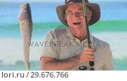 Купить «Man having just caught a fish», видеоролик № 29676766, снято 15 ноября 2010 г. (c) Wavebreak Media / Фотобанк Лори