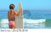 Купить «Woman holding her surfboard looking at the sea», видеоролик № 29676814, снято 15 ноября 2010 г. (c) Wavebreak Media / Фотобанк Лори