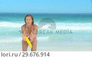 Купить «Woman in stripped swim suit playing frisbee», видеоролик № 29676914, снято 15 ноября 2010 г. (c) Wavebreak Media / Фотобанк Лори