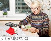 Женщина пенсионного возраста с квитанциями на оплату и российскими деньгами. Стоковое фото, фотограф Элина Гаревская / Фотобанк Лори