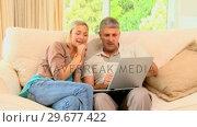 Купить «Couple enjoying pictures on laptop on sofa», видеоролик № 29677422, снято 6 ноября 2010 г. (c) Wavebreak Media / Фотобанк Лори