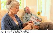 Retired woman knitting while her husband sleeps. Стоковое видео, агентство Wavebreak Media / Фотобанк Лори