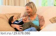 Купить «Mother bottlefeeding her son», видеоролик № 29678086, снято 6 ноября 2010 г. (c) Wavebreak Media / Фотобанк Лори