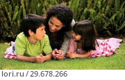 Купить «Young woman lying on the lawn chatting with her children», видеоролик № 29678266, снято 5 ноября 2010 г. (c) Wavebreak Media / Фотобанк Лори