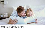 Купить «Cute child reading a book to his father», видеоролик № 29678494, снято 2 ноября 2011 г. (c) Wavebreak Media / Фотобанк Лори