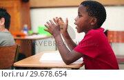 Купить «Pupil sitting at his table», видеоролик № 29678654, снято 5 ноября 2011 г. (c) Wavebreak Media / Фотобанк Лори
