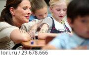 Купить «Happy teacher helping a blonde pupil», видеоролик № 29678666, снято 5 ноября 2011 г. (c) Wavebreak Media / Фотобанк Лори