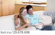 Купить «A couple watching TV with popcorn», видеоролик № 29678698, снято 3 ноября 2011 г. (c) Wavebreak Media / Фотобанк Лори