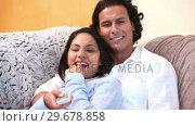Купить «Couple watching a funny movie together», видеоролик № 29678858, снято 3 ноября 2011 г. (c) Wavebreak Media / Фотобанк Лори