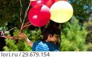 Купить «Boy holding balloons in slow motion», видеоролик № 29679154, снято 16 ноября 2011 г. (c) Wavebreak Media / Фотобанк Лори