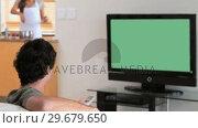 Купить «Man watching the television while his wife is cooking», видеоролик № 29679650, снято 4 ноября 2011 г. (c) Wavebreak Media / Фотобанк Лори