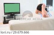 Купить «Man watching the television while speaking», видеоролик № 29679666, снято 4 ноября 2011 г. (c) Wavebreak Media / Фотобанк Лори