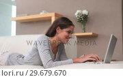 Купить «Brunette haired woman typing on her laptop», видеоролик № 29679670, снято 4 ноября 2011 г. (c) Wavebreak Media / Фотобанк Лори