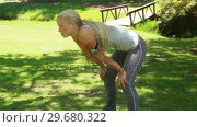 Купить «Woman catching her breath as she leans over and then lowers her head», видеоролик № 29680322, снято 17 ноября 2011 г. (c) Wavebreak Media / Фотобанк Лори