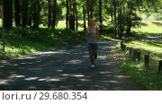 Купить «A woman jogs in the park and then is jogging on a main road afterwards», видеоролик № 29680354, снято 17 ноября 2011 г. (c) Wavebreak Media / Фотобанк Лори