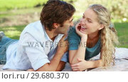 Купить «A couple lying on the ground share a kiss and then look at the camera», видеоролик № 29680370, снято 17 ноября 2011 г. (c) Wavebreak Media / Фотобанк Лори