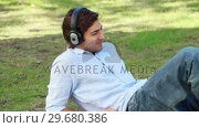 Купить «A man lies on the ground listening to his headphones», видеоролик № 29680386, снято 17 ноября 2011 г. (c) Wavebreak Media / Фотобанк Лори