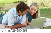 Купить «A man lies with a laptop as his girlfriend lies beside him and they look into the camera», видеоролик № 29680398, снято 17 ноября 2011 г. (c) Wavebreak Media / Фотобанк Лори