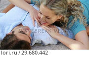 Купить «A woman lying on a mans chest talks to him as they smile», видеоролик № 29680442, снято 17 ноября 2011 г. (c) Wavebreak Media / Фотобанк Лори