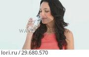 Купить «Attractive young woman drinks water», видеоролик № 29680570, снято 11 ноября 2011 г. (c) Wavebreak Media / Фотобанк Лори