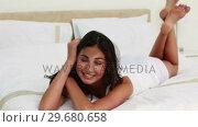 Купить «Brunette haired woman posing while lying down», видеоролик № 29680658, снято 11 ноября 2011 г. (c) Wavebreak Media / Фотобанк Лори